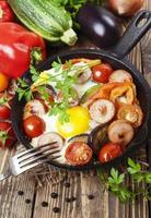 Fried eggs with vegetables and sausage