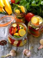 Preparing preserves of pickled zucchini in jars with spices, gar photo