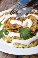 Zucchini pancakes with sour cream closeup on the table photo