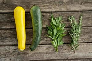 Courgettes and herbs on wooden board