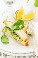 Appetizing sandwich with chicken, spinach, avocado and poppy seeds photo