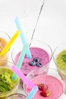 Assorted fruit and vegetable shakes on white table