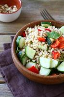Tasty pearl barley salad with vegetables in a wooden bowl