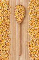 cuchara de madera con maíz acostado foto