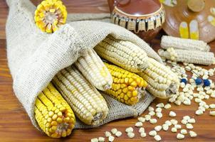 Dried corn cobs in a bag on a wooden table photo