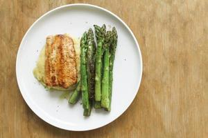 Seasoned roasted green asparagus with grilled salmon on polenta photo