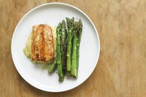 espárragos verdes asados sazonados con salmón a la parrilla en polenta foto