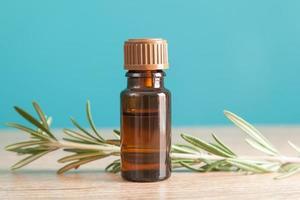 botella con aceite aromático y romero foto