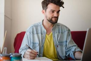 handsome hipster modern man working home using laptop photo
