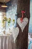 Wicker hearts hanging on tree in wedding hall.