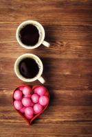 Sweet candies in heart shaped box and cups of coffe photo