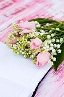 notebook and a bouquet of lilies of valley and tulips photo