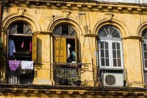 fachada de um edifício colonial antigo e degradado em yangon, myanmar.