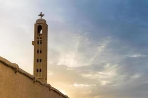 Monasterio copto con cruz de piedra de la torre al atardecer foto