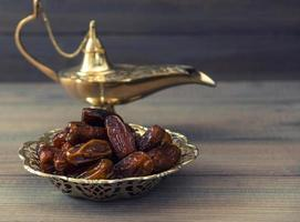 Dates and golden arabian lamp on wooden background photo