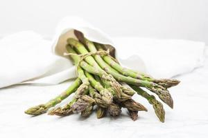 Organic green asparagus wrapped in white napkin