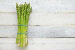 Bunch of fresh asparagus on a white wooden table. photo