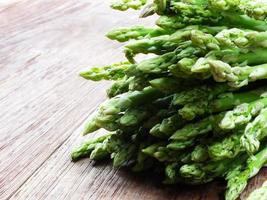 green raw asparagus on wooden table background photo