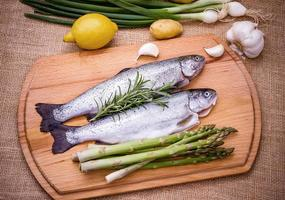 Two raw trout with green asparagus, lemon and garlic