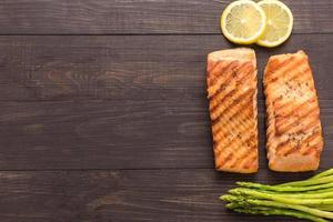 Grilled salmon with lemon, asparagus on wooden background