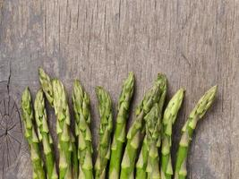 resh green asparagus on old wood board, photo