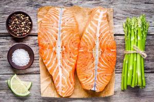 fresh raw salmon fillet with asparagus and lime top view
