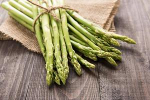 Bunch of fresh green asparagus on a rustic wooden table photo