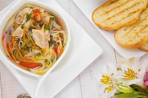 rustic chicken soup with noodles and over wooden background