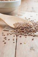 Organic lentils with wooden false on burlap background