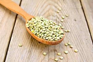 Lentils green in wooden spoon on board