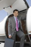 Asian businessman getting off airplane. photo