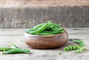 wooden bowl full  of green peas pods photo