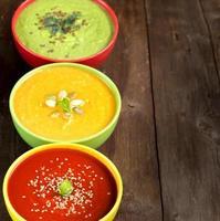 tres sopas frescas en una mesa de madera foto