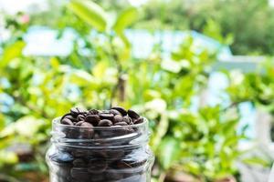 granos de café tostados en botella de vidrio y fondo verde borroso foto