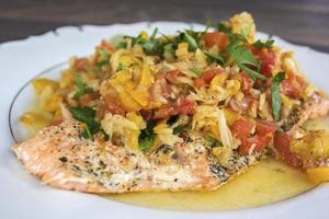 salmón al horno de estilo griego con tomates y zanahorias foto