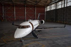 Business jet airplane stays in hangar. photo