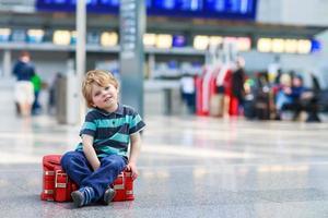 Little Boy va de viaje de vacaciones con maleta en el aeropuerto foto