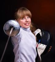 Smiling girl in fencing wear pointing epee at camera
