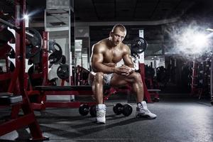 very power athletic guy, relaxing after workout in sport hall photo