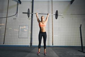 joven mujer fuerte haciendo levantamiento de pesas foto