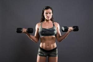 Fitness woman weight lifting with dumbbells. photo