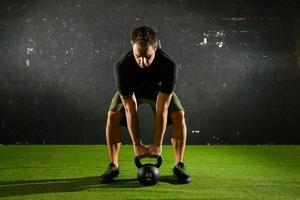 Athlete lifting heavy weight with Kettle-bell photo