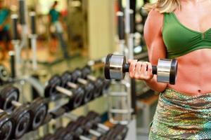 Frau, die Bizeps im Fitnessstudio übt