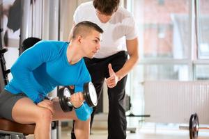 Man doing weights lifting with trainer photo