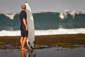 Surfer with surfboard on a coastline photo