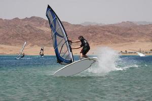 saltar. Joven windsurfista. foto