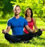 joven hombre y mujer haciendo yoga en el verano soleado