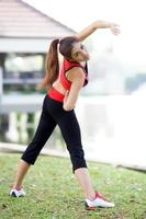 Young pretty woman doing yoga exercises in park