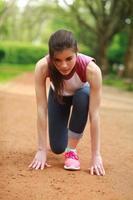 ragazza concentrata che si prepara per iniziare a correre, allenandosi nel parco