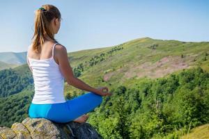 mujer joven medita en la cima de la montaña